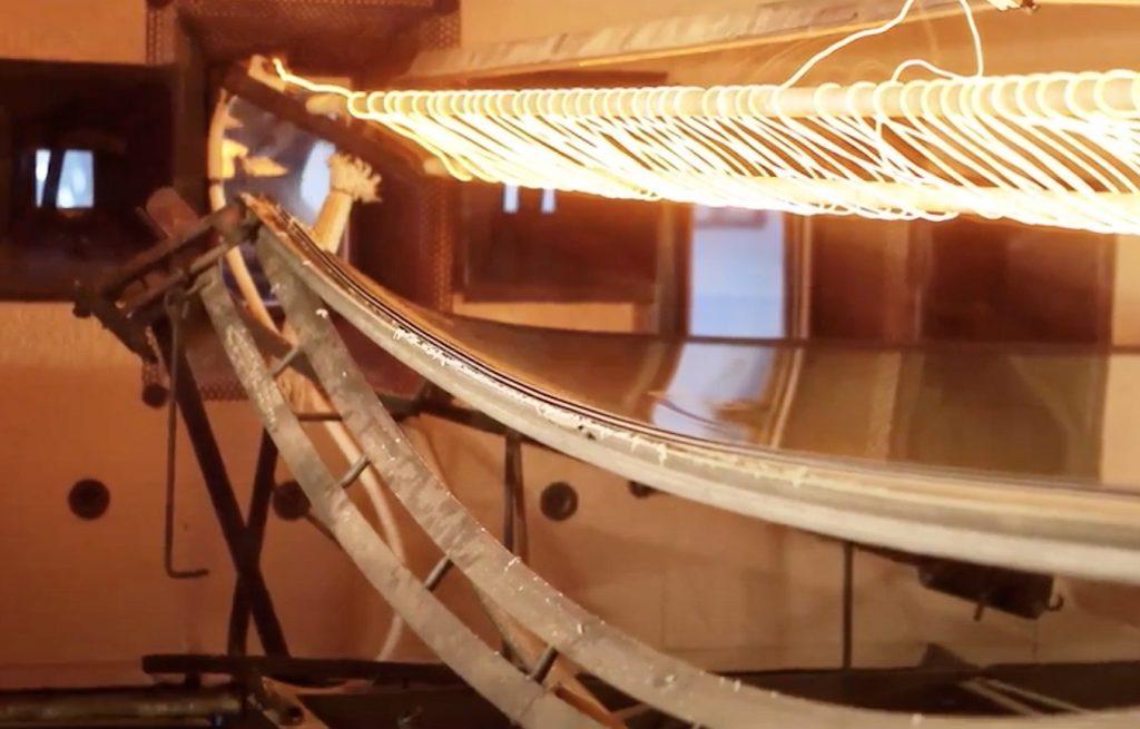 """Les deux feuilles de verre d'un pare-brise, posées sur un """"squelette"""", à la sortie du four."""